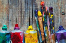 Tubes of oil paint and artist paint brushes closeup on wooden background. Retro styled.